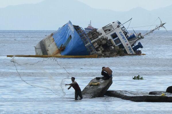 Un pescador cerca de un barco en la bahía de Manila, Filipinas.  - Sputnik Mundo