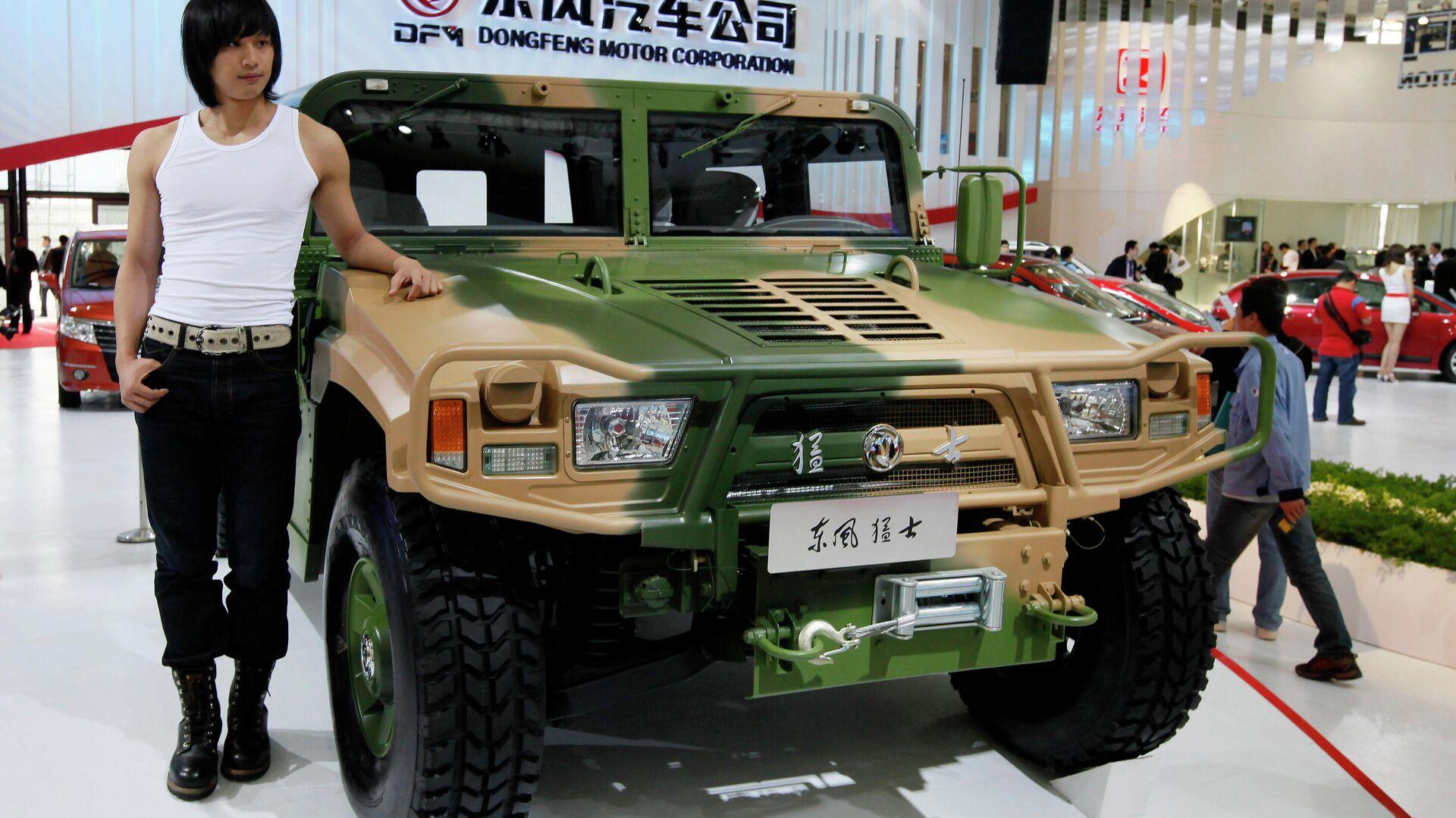 Una persona posa al lado del 'Hummer' militar de Dongfeng Motor, en el Salón Internacional del Automóvil de Shanghai de 2009 - Sputnik Mundo, 1920, 12.07.2021