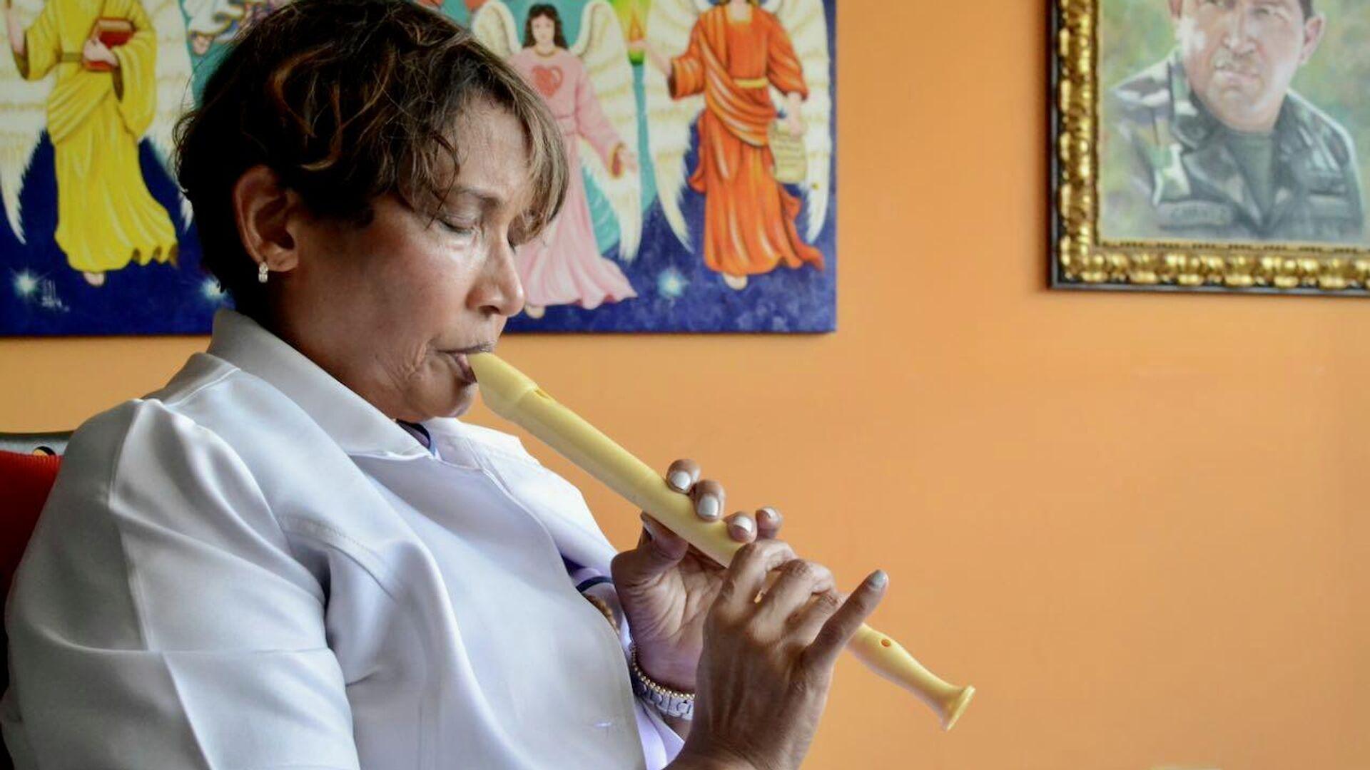 La doctora Zayra Medina ejecuta una flauta en su despacho - Sputnik Mundo, 1920, 12.07.2021