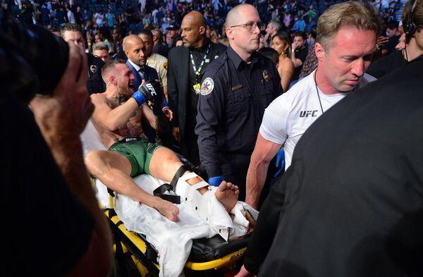 El luchador irlandés Conor McGregor abandona el octágono en camilla tras fracturarse la pierna en su pelea contra Dustin Poirier en el torneo UFC 264. - Sputnik Mundo