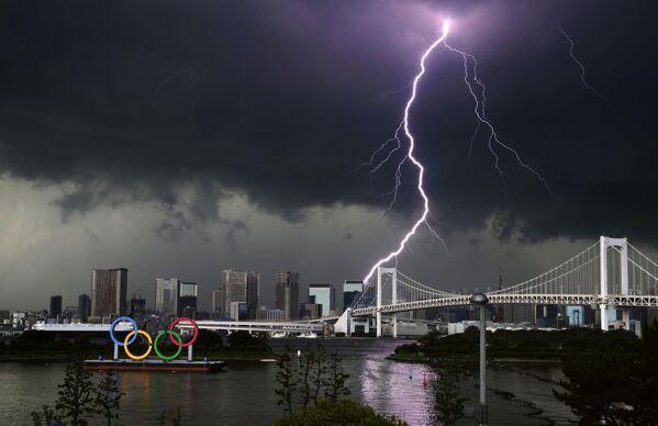 Un rayo alcanza el puente Rainbow Bridge y el monumento de los aros olímpicos en Tokio, Japón. - Sputnik Mundo