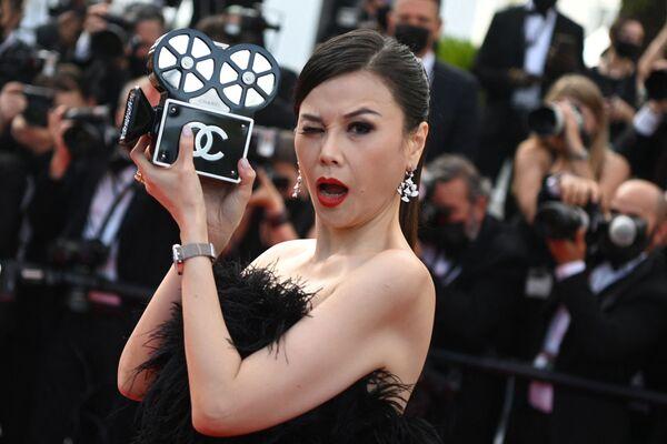 Una asistente al festival muestra un clutch de Chanel con forma de cámara. - Sputnik Mundo