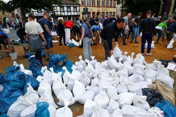 Unos vecinos de Erftstadt colocan sacos de arena para parar la crecida del agua. - Sputnik Mundo