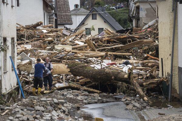 En Schuld, al menos 70 personas siguen desaparecidas luego de que las fuertes lluvias destruyeran sus casas. Y en Leverkusen y Eschweiler, las autoridades tuvieron que evacuar de los hospitales locales a unos 700 pacientes. En la foto: los escombros en una calle de Schuld. - Sputnik Mundo
