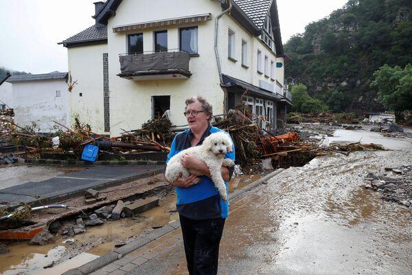 Un hombre con su perro en una calle inundada de Schuld. - Sputnik Mundo