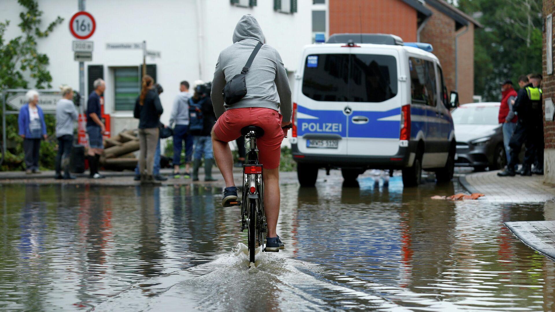 Un ciclista conduce por una calle inundada debido a las fuertes lluvias en Erftstadt-Blessem, Alemania, 16 de julio de 2021 / Foto de archivo - Sputnik Mundo, 1920, 17.07.2021
