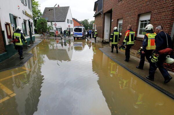 Varios bomberos caminan por una calle inundada en Erftstadt-Blessem, Alemania, el 16 de julio de 2021 / Foto de archivo - Sputnik Mundo