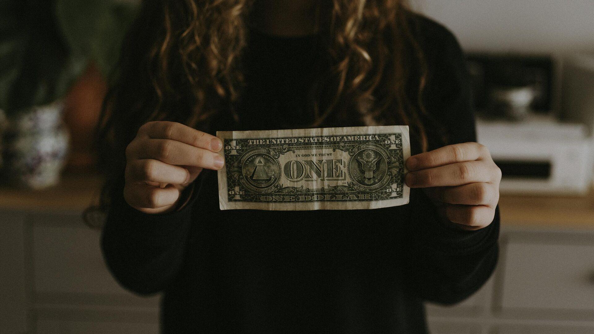 Una mujer sostiene un billete de un dólar () - Sputnik Mundo, 1920, 18.07.2021