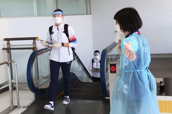 Después de hacerse el test, los atletas atraviesan un pasillo donde está prohibido detenerse, y los voluntarios los acompañan con amabilidad y al mismo tiempo con insistencia hasta la salida al aparcamiento. En la foto: un miembro de la selección olímpica de Corea del Sur en el aeropuerto de Narita. - Sputnik Mundo