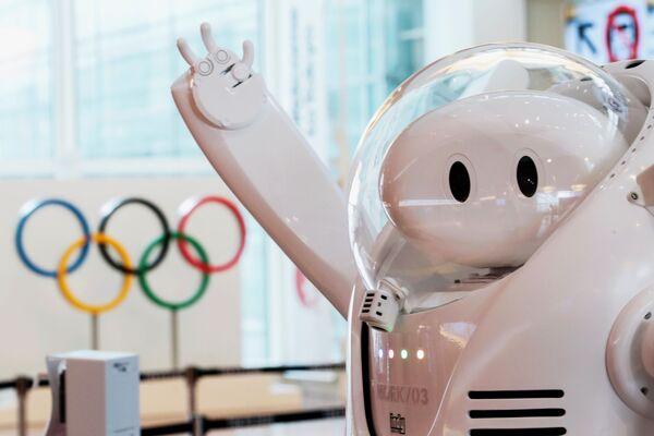 """El presidente del Comité Olímpico Internacional (COI), Thomas Bach, advirtió que solo el 0,1% de quienes llegaron a Japón estaba contagiado. No obstante, los críticos de los JJOO el 18 de julio se dirigieron hacia el Palacio de Akasaka, donde recibieron al presidente del COI con carteles donde estaba escrito: """"¡Detenga los Juegos Olímpicos!"""", """"¡proteja las vidas y no los Juegos Olímpicos!"""", """"¿señor Bach, qué pretende? y """"¡por favor, vuelva a casa!"""". En la foto: un robot cerca de un mostrador de información en el aeropuerto de Haneda, Tokio, antes de la llegada de Bach. - Sputnik Mundo"""