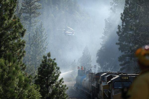 La mayoría de los incendios se registraron en los estados de Montana (18), Idaho (17), California (9) y Oregón (9). En la foto: Los bomberos protegen las vías e intentan extinguir los incendios forestales en los estados afectados. - Sputnik Mundo