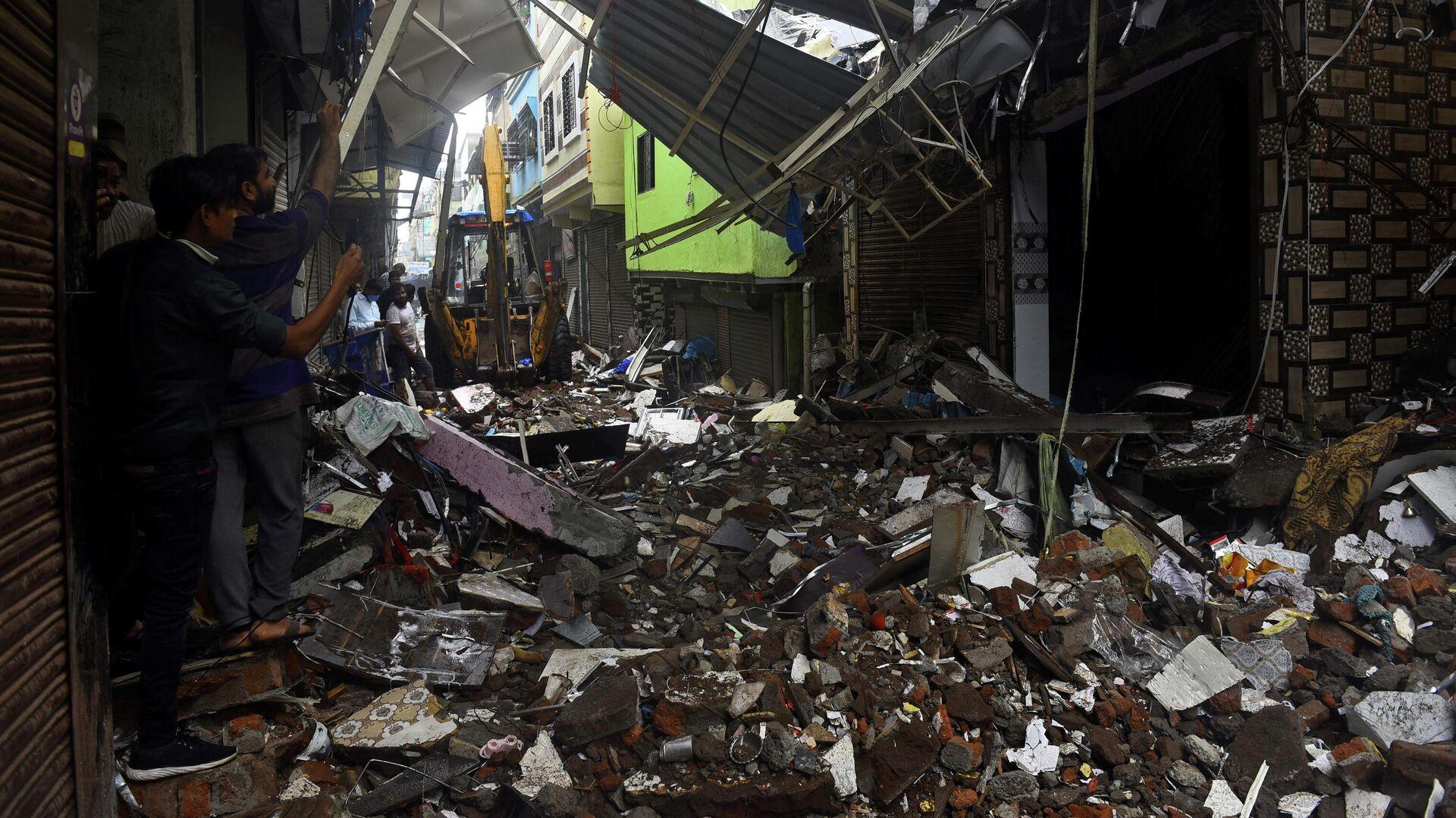 La gente usa sus teléfonos móviles para tomar fotos de un edificio derrumbado tras las lluvias en Mumbai, India, el 23 de julio de 2021 - Sputnik Mundo, 1920, 24.07.2021