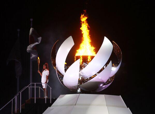 La tenista japonesa y ganadora de cuatro Grand Slam, Naomi Osaka, sostiene la antorcha olímpica después de encender el pebetero. - Sputnik Mundo