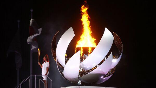 Наоми Осака из Японии держит олимпийский факел после зажжения олимпийского котла на церемонии открытия  - Sputnik Mundo