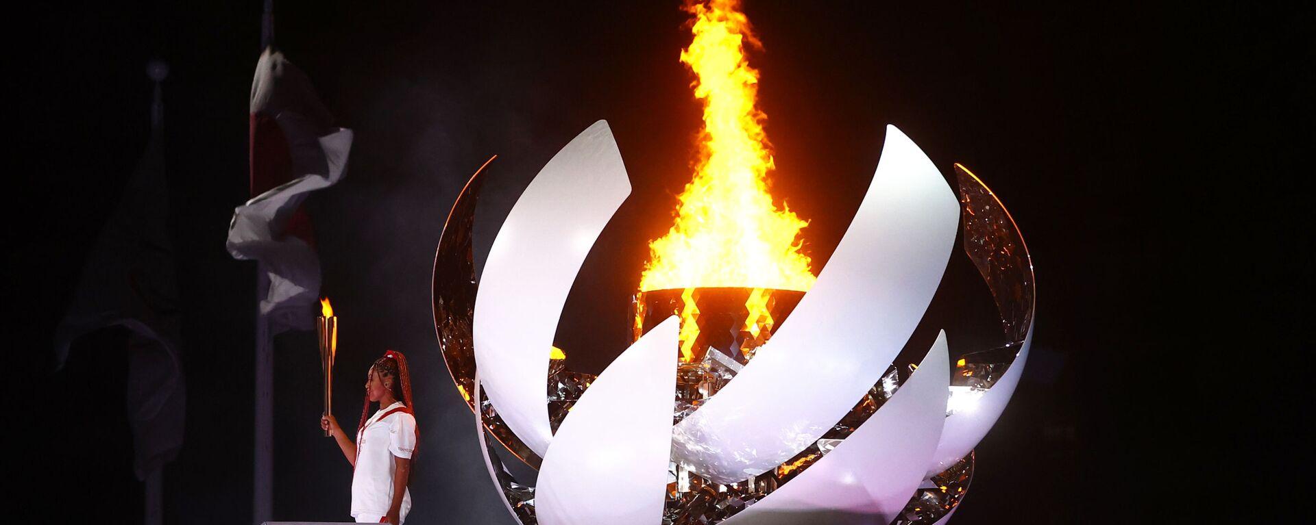 Наоми Осака из Японии держит олимпийский факел после зажжения олимпийского котла на церемонии открытия  - Sputnik Mundo, 1920, 24.07.2021