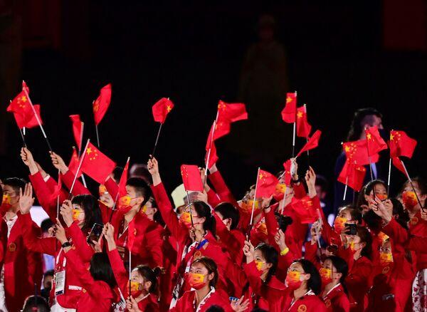 Miembros de la delegación de China ondean banderas al entrar al Estadio Olímpico. - Sputnik Mundo