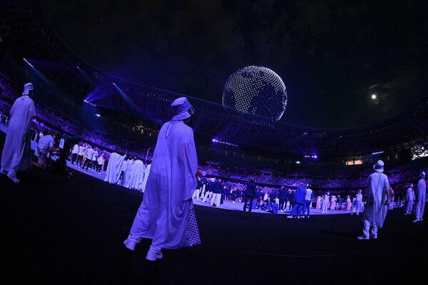 Los atletas y los voluntarios observan cómo los drones vuelan para formar un globo en el cielo sobre el Estadio Olímpico de Tokio. - Sputnik Mundo