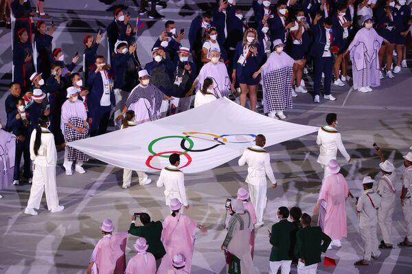 Varios atletas portan la bandera olímpica durante la ceremonia de inauguración de los JJOO de Tokio.  - Sputnik Mundo