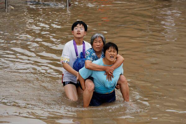 Más de 157.000 personas necesitan asistencia de emergencia. En la foto: residentes locales cruzan una calle inundada en Zhengzhou, provincia de Henan. - Sputnik Mundo