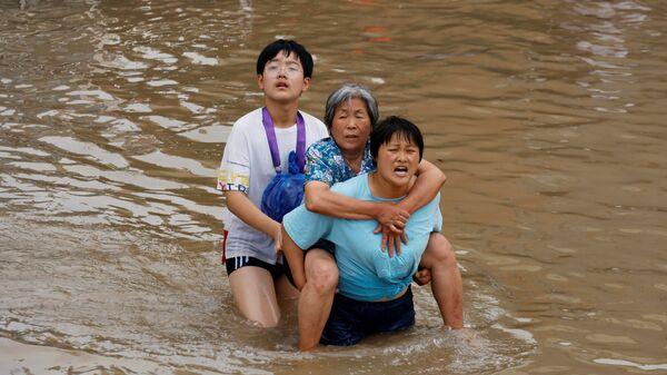 Женщина несет пожилую женщину  через паводковые воды после проливного дождя в Чжэнчжоу, провинция Хэнань, Китай - Sputnik Mundo