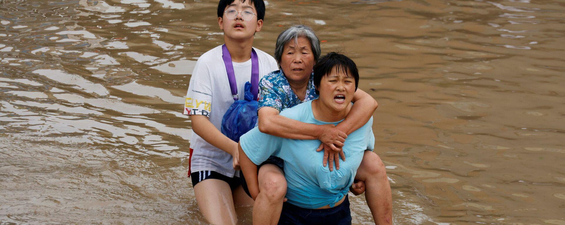 Женщина несет пожилую женщину  через паводковые воды после проливного дождя в Чжэнчжоу, провинция Хэнань, Китай - Sputnik Mundo, 1920, 26.07.2021