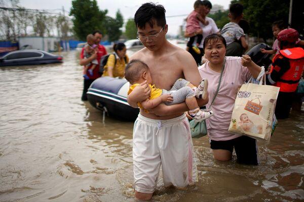 Los lugareños cruzan una calle inundada en Zhengzhou. - Sputnik Mundo