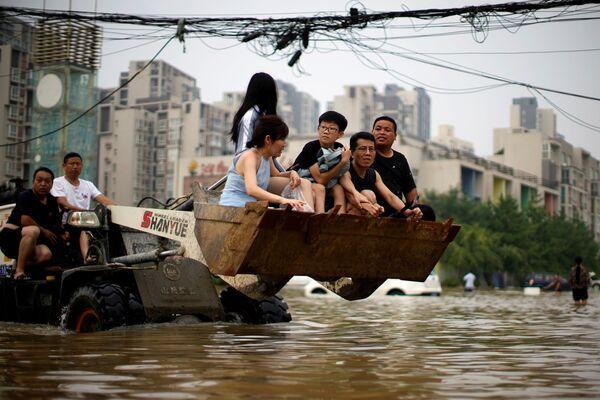 Residentes locales se mueven en una carretilla elevadora a través de un área inundada en Zhengzhou. - Sputnik Mundo