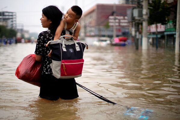 Una mujer con un niño y sus pertenencias recorre una calle inundada en Zhengzhou. - Sputnik Mundo