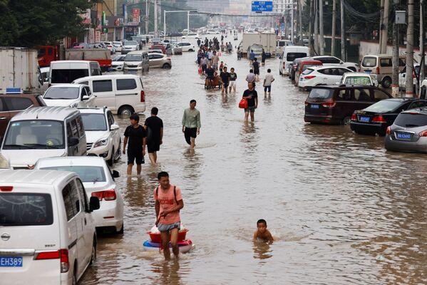 En muchas localidades de la provincia, en particular en la ciudad de Zhengzhou, el suministro de agua y electricidad, así como las comunicaciones aún no se han restablecido por completo. En la imagen: las personas caminan por una calle inundada en Zhengzhou. - Sputnik Mundo