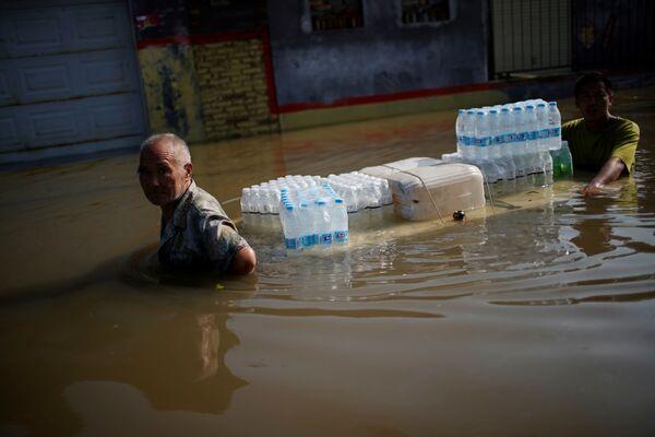 La gente traslada agua potable a través de un área inundada en Xinxiang. - Sputnik Mundo