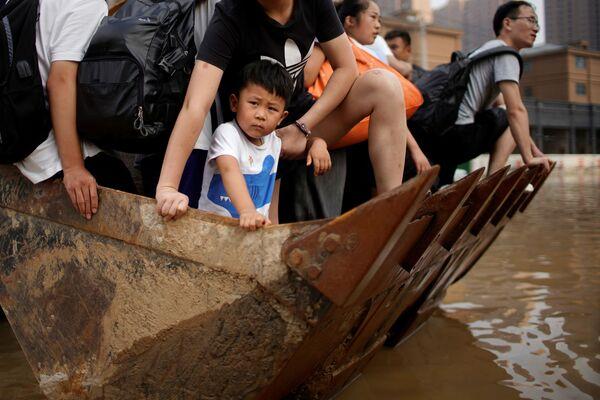Los residentes locales se mueven en una carretilla elevadora a través de un área inundada en Zhengzhou. - Sputnik Mundo