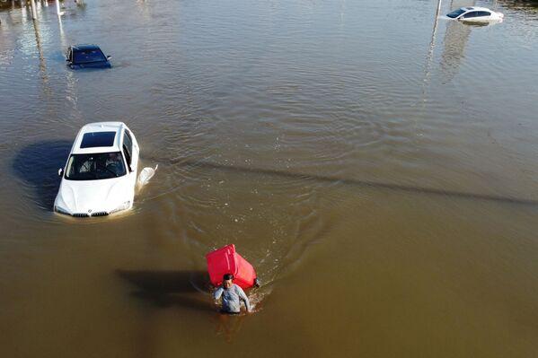 El 17 de julio fuertes lluvias azotaron la parte central de China. La provincia de Henan fue la más afectada. Algunas estaciones meteorológicas de la ciudad de Zhengzhou han registrado un récord histórico de precipitación media por día. En la foto: un hombre con un cubo de basura camina por una calle inundada en Xinxiang. - Sputnik Mundo