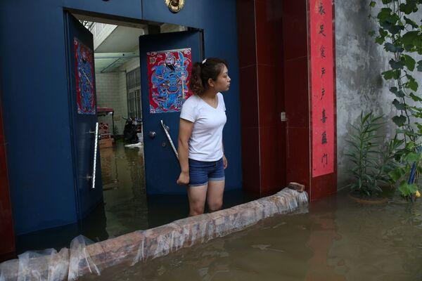 Una niña en una casa inundada en Xinxiang. - Sputnik Mundo