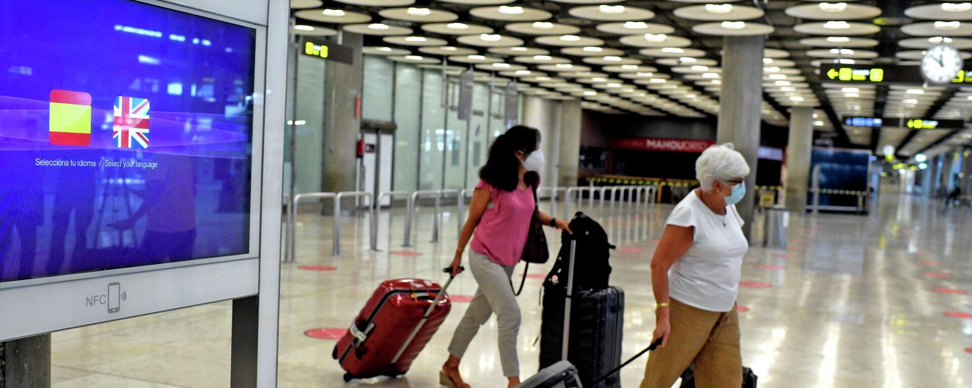 Dos pasajeras con maletas en la terminal T1 del Aeropuerto de Madrid-Barajas Adolfo Suárez, en Madrid (España), a 27 de julio de 2020. Desde ayer está en vigor la orden del Gobierno del Reino Unido que impone a los viajeros procedentes de España pasar dos semanas en cuarentena por si están infectados con coronavirus. - Sputnik Mundo, 1920, 26.07.2021