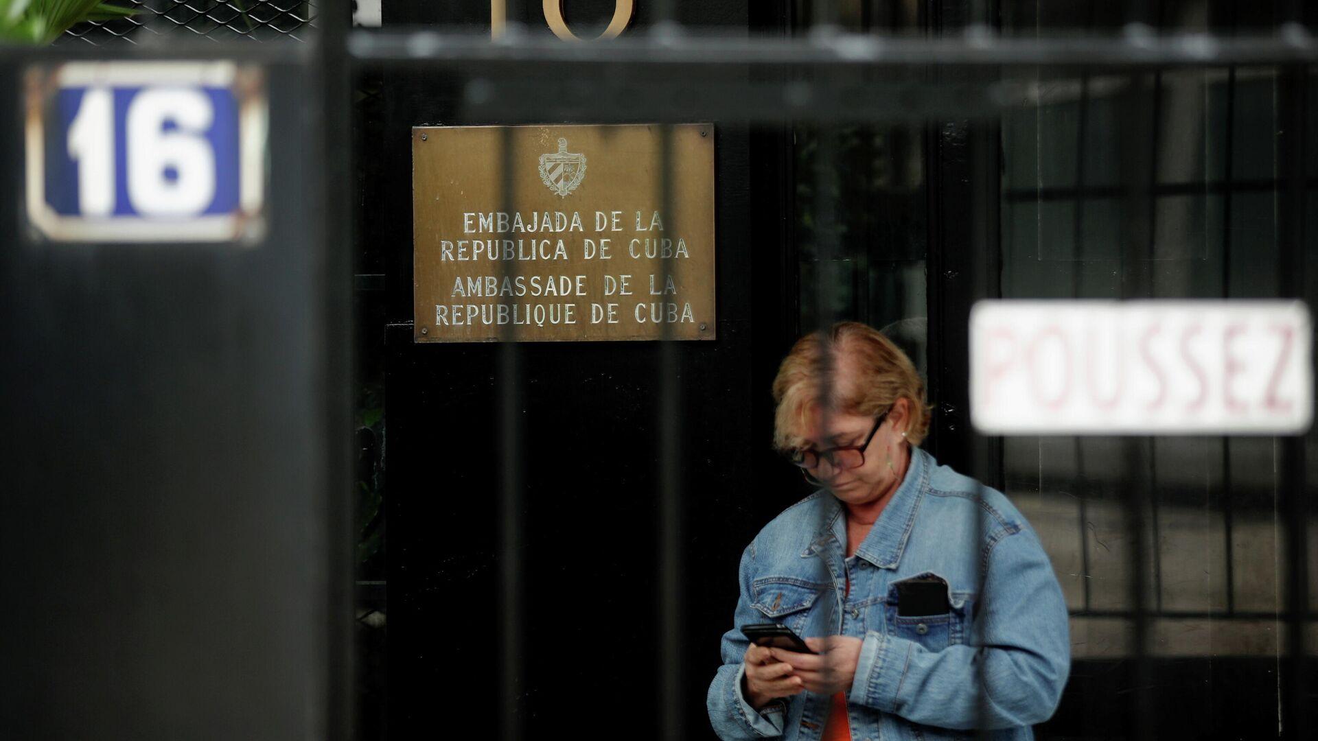 Una mujer usa un teléfono móvil cerca de la Embajada de Cuba tras un ataque con cócteles molotov contra su edificio, París, Francia, el 27 de julio de 2021 - Sputnik Mundo, 1920, 27.07.2021