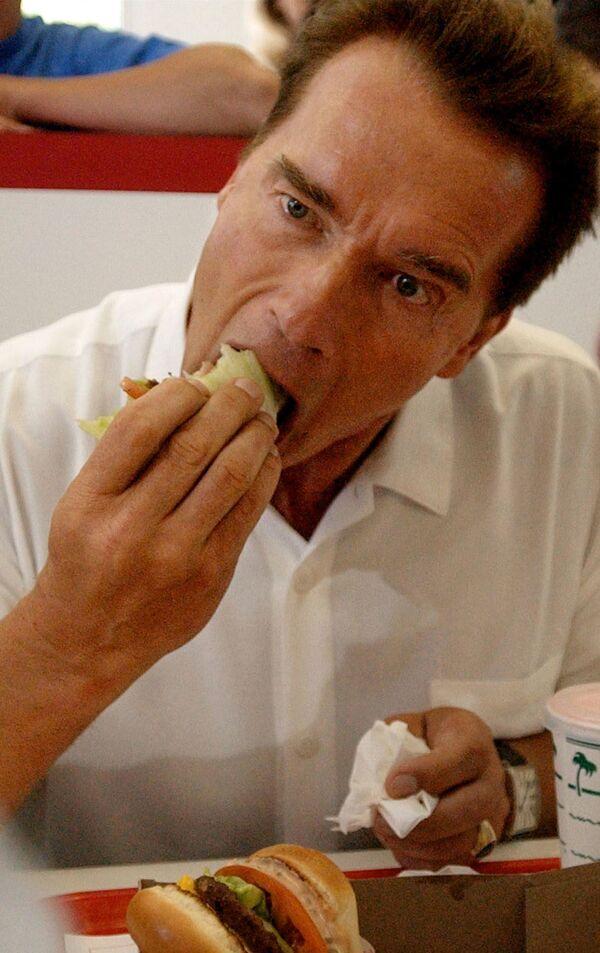 La hamburguesa inició su camino hacia la fama en 1904, tras la Feria Mundial de San Luis (en Missouri). En la foto, el gobernador de California Arnold Schwarzenegger se come una hamburguesa envuelta en lechuga en el In-N-Out Burger de Merced de California en 2003. - Sputnik Mundo