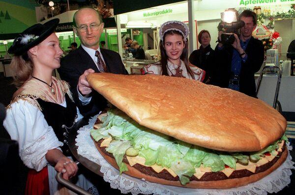 Se dice que la hamburguesa nació el 27 de julio de 1900 porque fue entonces cuando Louis Lessing, el propietario de Louis' Lunch en New Haven (Connecticut), puso por primera vez un tradicional filete alemán entre dos panes redondos, añadió salsa y una hoja de lechuga. De esta forma, la hamburguesa se convirtió en un símbolo de la gastronomía del país. En la foto: el ministro alemán de Agricultura, Jochen Borchert, junto a una hamburguesa gigante en la mayor feria mundial de alimentación y agricultura, la Gruene Woche de Berlín, en 1997. - Sputnik Mundo