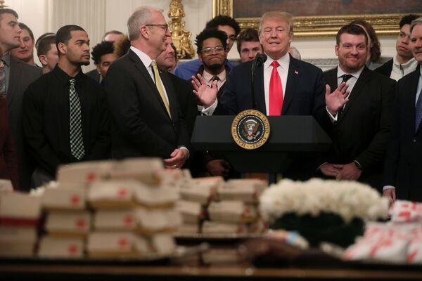 Actualmente la hamburguesa es considerada un símbolo de la cultura estadounidense. Se trata de un plato que se puede pedir tanto en los bares de carretera como en los restaurantes caros. En la imagen: el presidente de Estados Unidos, Donald Trump, durante una reunión en la Casa Blanca con los jugadores del equipo de fútbol americano de la Universidad de Dakota del Norte en 2019. - Sputnik Mundo