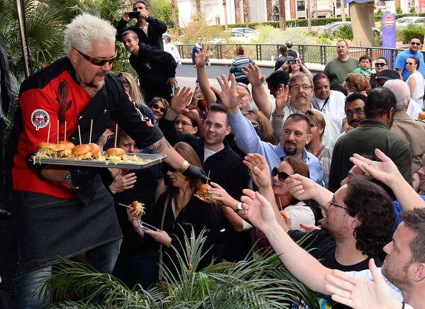 En Las Vegas está ubicado el local Heart attack Grill. Una hamburguesa estándar pesa allí casi un kilo y tiene un valor energético de 8.000 calorías. En la foto, el chef y presentador de televisión Guy Fieri sirve hamburguesas a los clientes en su restaurante Vegas Kitchen & Bar en Las Vegas en 2014. - Sputnik Mundo