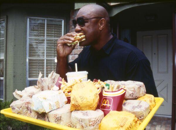 Los locales de McDonald's se extendieron rápidamente por todo el mundo gracias a las franquicias, y la empresa y sus hamburguesas se convirtieron en un barómetro no solo de la economía estadounidense, sino también de la mundial. En la foto: el campeón mundial y olímpico de pesos pesados George Foreman en un restaurante de McDonald's en Texas en 1991. - Sputnik Mundo