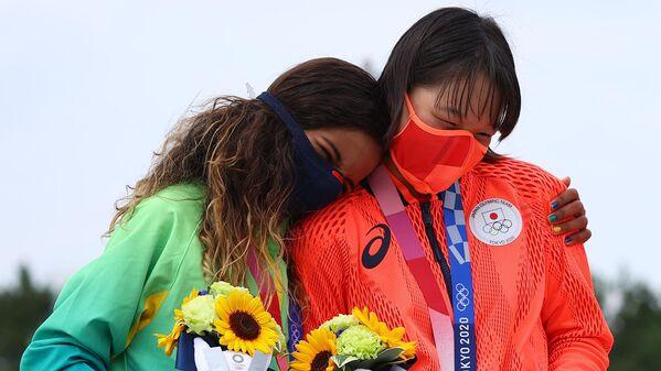 La brasileña Rayssa Leal y la japonesa Momiji Nishiya, ambas de 13 años, celebran sus medallas —plata y oro, respectivamente— en la modalidad calle del skateboarding femenino. - Sputnik Mundo