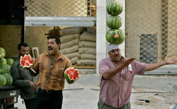Un vendedor de frutas hace equilibrios con varias sandías en la cabeza para atraer a los clientes en Palestina. - Sputnik Mundo