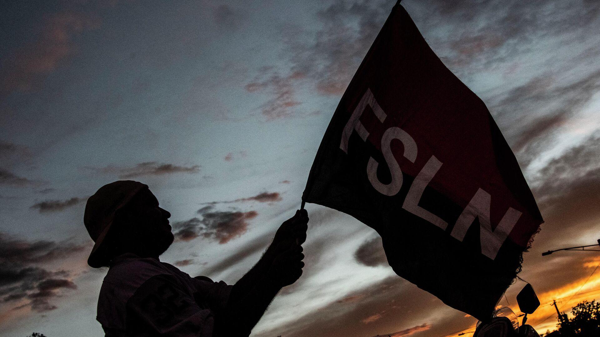 Un partidario del presidente nicaragüense Daniel Ortega ondea una bandera del Frente Sandinista de Liberación Nacional (FSLN) - Sputnik Mundo, 1920, 04.08.2021