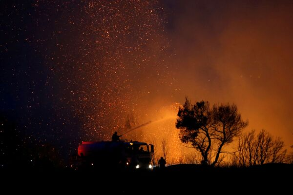 Un equipo de bomberos intenta sofocar un incendio forestal en Varympompi. - Sputnik Mundo