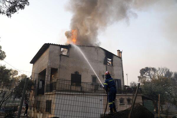 Un bombero intenta apagar una casa en llamas en Varympompi, al norte de Atenas. - Sputnik Mundo