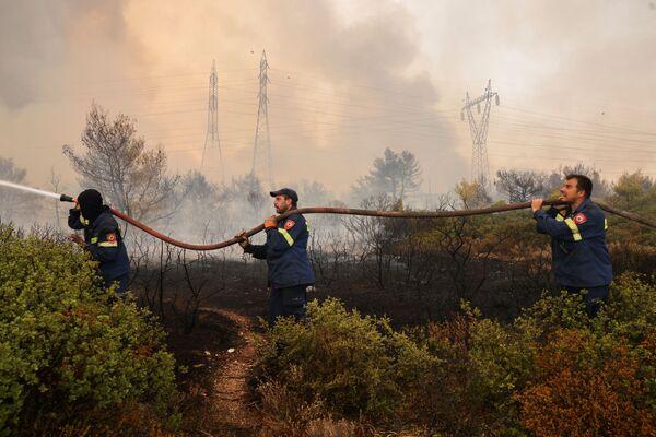 Unos bomberos voluntarios portan una manguera. - Sputnik Mundo