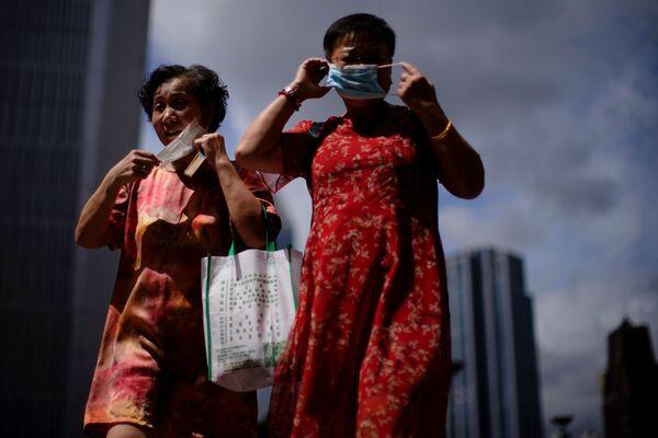 El 3 de agosto, las autoridades de Wuhan notificaron tres casos de infección confirmados y cinco asintomáticos. En la foto: dos mujeres se ajustan sus mascarillas mientras caminan por la calle, tras los nuevos casos de coronavirus, en Shanghái, China. - Sputnik Mundo