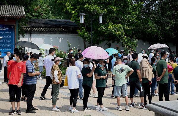 Una de las calles afectadas en Wuhan fue declarada zona de riesgo medio, con la imposición de restricciones correspondientes. En la foto: varias personas hacen cola para realizarse la prueba de coronavirus en un parque de Pekín. - Sputnik Mundo