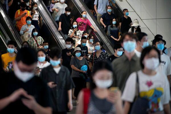 Varias ciudades y provincias emitieron alertas e instaron a tomar medidas para frenar la propagación de la nueva cepa de coronavirus. En la foto: varias personas con mascarillas suben las escaleras de una estación de metro en Shanghái. - Sputnik Mundo