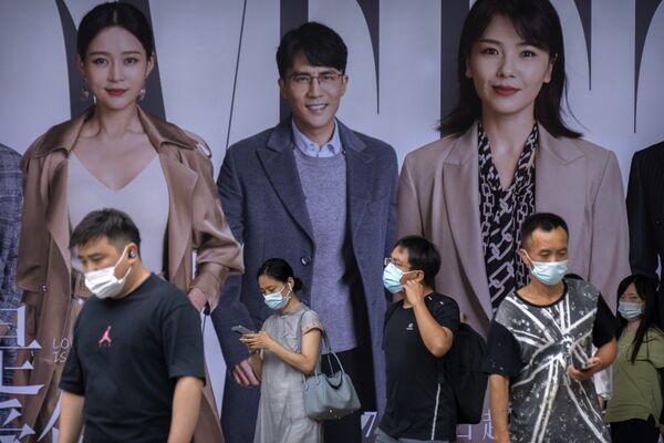Desde que se produjo el primer brote a fines de 2019, se registraron en Wuhan 50.399 casos de COVID-19, con 3.869 fallecimientos. En la foto: los habitantes con sus mascarillas pasan por delante de un cartel publicitario en una estación de metro durante la hora pico en Pekín. - Sputnik Mundo